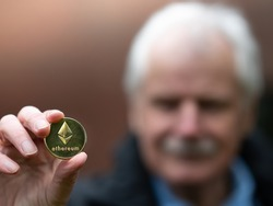 Symbol for Ethereum as a Retirement Plan Investment. Old man holding a Ethereum coin.