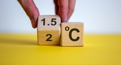 Symbol for limiting global warming. Male hand turnee a cube and changes the expression '2 C' to '1.5 C', or vice versa. Concept. Beautiful yellow table, white background, copy space.