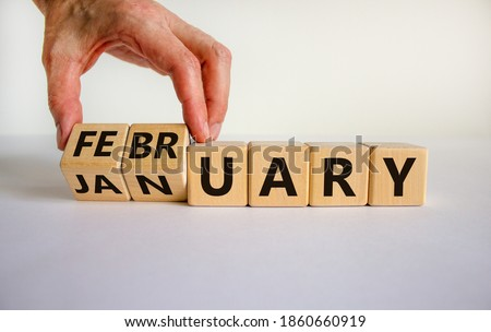 Symbol for the change from January to February. Male hand flips wooden cubes and changes the inscription 'January' to 'February'. Beautiful white background, copy space.