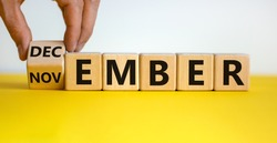 Symbol for the change from November to December. Male hand flips wooden cubes and changes the inscription 'november' to 'december'. Beautiful yellow table, white background, copy space.