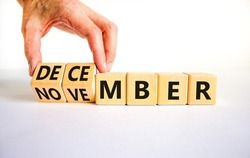 Symbol for the change from November to December, winter. Businessman turns wooden cubes and changes the word 'November' to 'December'. Beautiful white background, copy space. Happy December concept.