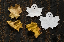 Symbol Halloween - a ghost made of white colored maple leaves and dry leaves on a dark wooden background