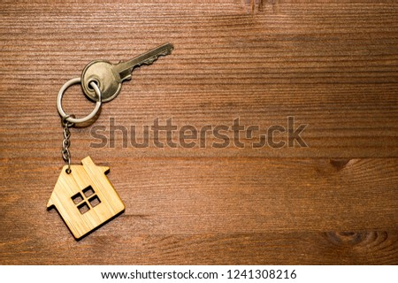 Symbol of a bamboo house with a metal key on a brown vintage wooden background. Lighting gradient. The concept of selling real estate with the transfer of ownership.