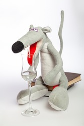 symbol of 2020, a cute gray rat with a long tail sits on a stack of books on a white background close-up. A large red tongue inserted into an elegant glass cup with a long stem