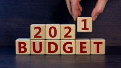 Symbol of 2021 budget. Male hand puts a wooden cube on other cubes with the word 'Budget 2021'. Beautiful dark wooden background, copy space. Business and 2021 new year budget.