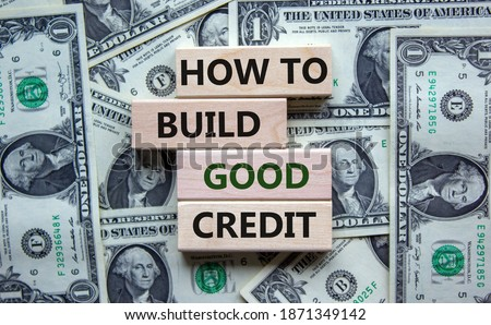 Symbol of building success foundation. Stack of wooden blocks. Words 'how to build good credit'. Beautiful background from dollar bills. Business and build good credit concept.