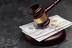 Symbol of court and justice, wooden gavel, banknotes on black background,