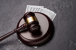 Symbol of court and justice, wooden gavel, dollars