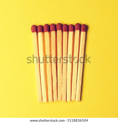 Symbol of danger with matches on yellow  background top view , pile of match arrange in a row , unlit matches