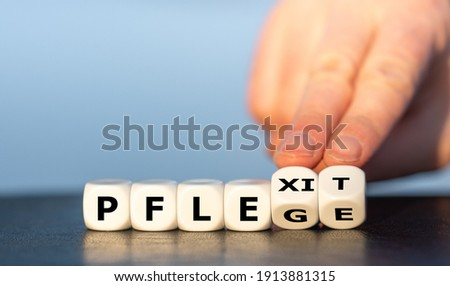 Symbol of health care workers quitting the job. Hand turns dice and changes the German expression 'Pflege' (care) to 'Pflexit' (word combination of care and exit).  Stock photo ©