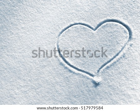Symbol of heart on the background of fresh snow texture in blue tone. Merry Christmas or Valentine's Day Concept. Top view, high resolution product