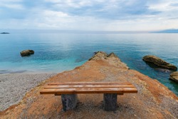 symbol of loneliness, lonely bench in the Crete island beach. Day foto. Greece vacation, copy space.