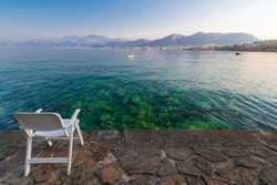 symbol of loneliness, lonely chair in the Crete island beach in sunset time. Greece vacation, copy space.