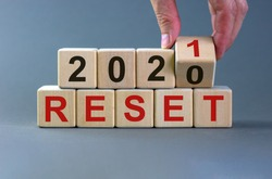 Symbol of 2021 reset. Male hand flips wooden cubes and changes the inscription 'Reset 2020' to 'Reset 2021'. Beautiful grey background, copy space. Business and 2021 reset concept.
