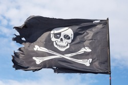Symbol of the pirates Jolly Roger against the sky.
