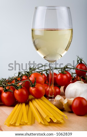 Symbolic arrangement of the Italian cuisine – pasta, garlic, tomatoes and white wine in a glass.