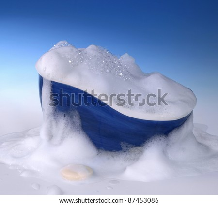 symbolic cleaning and washing background with bathtub,soap and lots of foam in blue gradient back