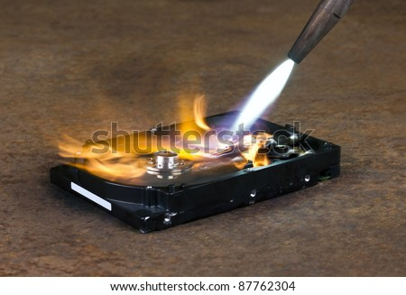 symbolic computer theme showing a welding torch tip and dashing flame burning a fixed hard disk wich is located on rusty metallic ground