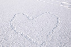 symbolic drawing of a heart on the snow, made by the steps of the feet. Footprints in the snow. Valentine's day concept, love symbol. Walking entertainment for a couple in love. space for text