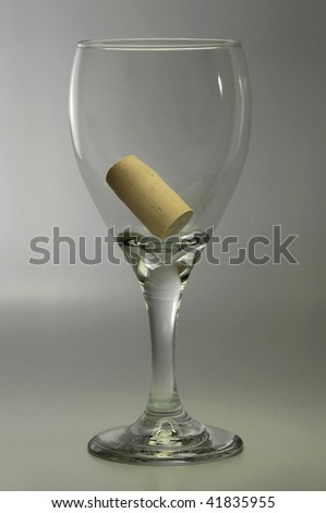 Symbolic empty wine glass containing the bottle cork