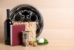 Symbolic Pesach (Passover Seder) items on wooden table, space for text