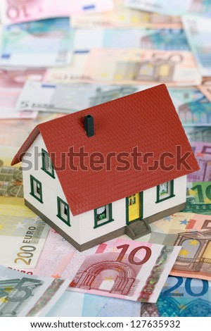 Symbolic picture for home financing with a building on Euro notes