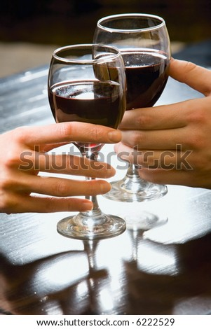 Symbolic picture of glasses of red wine in human hands