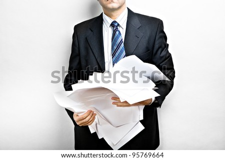Symbolic picture. Suited man holding stack of documents.