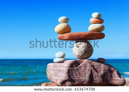 Symbolic scales of stones against the background of the sea and blue sky. Concept of harmony and balance. Pros and cons concept.