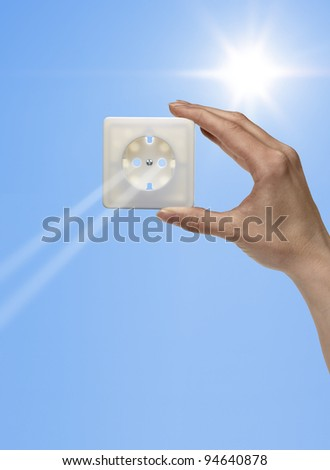symbolic solar energy theme showing the sun and sky with human hand holding a electrical socket while sunbeams falling through