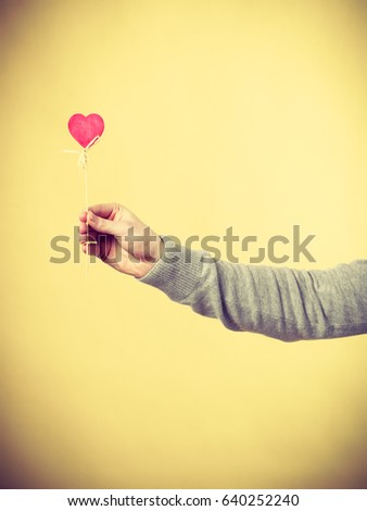 Symbolism romance relationship affection valentines concept. Male person holding heart on stick. Someone presenting love symbol on pole. #640252240
