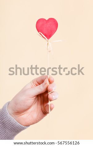 Symbolism romance relationship affection valentines concept. Person holding heart on stick. Someone presenting love symbol on pole. #567556126