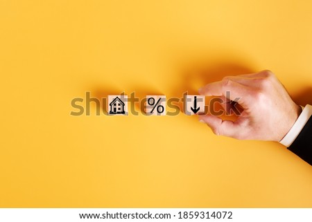 symbols house, percent and down arrow on wooden cubes and orange background. concept of low cost real estate Сток-фото ©
