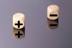 Symbols of black color plus and minus on wooden cubes on a mirror background.