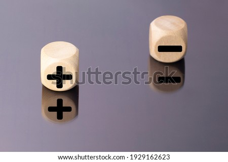 Symbols of black color plus and minus on wooden cubes on a mirror background. Stockfoto ©