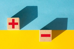 Symbols of red color plus and minus on wooden cubes on a yellow and blue background