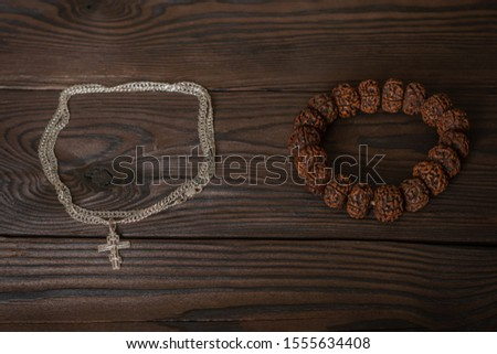 Symbols of religions, a Christian Orthodox cross on a chain around the neck and a Buddhist bracelet lie together on a wooden table. religious freedom day