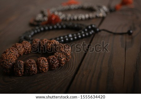 symbols of religions, Islamic rosary, Christian black rosary and a Buddhist bracelet lie together on a wooden table. focus on buddhist bracelet. religious freedom day