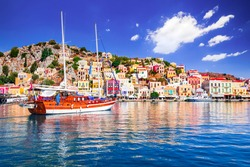 Symi Island, Greece. Greece islands holidays from Rhodos in Aegean Sea. Colorful neoclassical houses in bay of Symi. Holiday travel background.