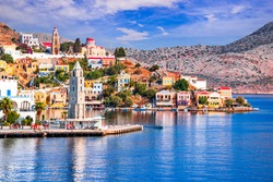 Symi Island, Greece. Greece islands holidays vacation travel tours from Rhodos island in Aegean Sea. Colorful neoclassical houses in bay of Symi.