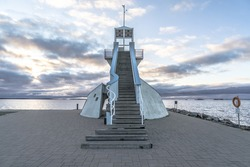 Symmetric lighthouse in Nallikari, Oulu, Finland. Scenic evening skyline over Baltic sea with clouds. Beautiful stairs to observation tower at the end of a paved dock