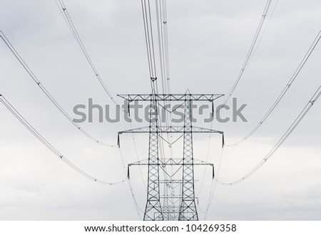 symmetric power lines against a cloudy sky