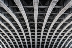 Symmetric steel framework under a bridge over the river Thames in London.