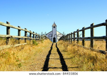 Symmetric view of a small wooden church in the prairies during autumn