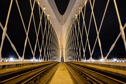 Symmetrical bridge construction in the night with bright lights, vibrat colors and rails in the center.