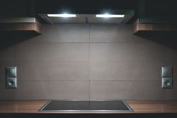 Symmetrical minimal kitchen shot with an absorber with lights on, a wooden work bench and an electrical induction hob. Kitchen interior design wallpaper/background with copy space.