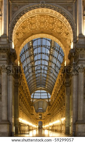 Symmetrical night shot of the hall of the landmark arcade or covered luxury shopping mall, Galleria Vittorio Emanuele II in Milan, Italy, showing the spectacular view of a golden gate to luxury
