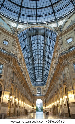Symmetrical night shot of the hall of the landmark arcade or covered shopping mall, Galleria Vittorio Emanuele II in Milan, Italy, showing the spectacular view of an almost golden gate to luxury