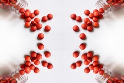 Symmetrical pattern with four quadrants like in a kaleidoscope of red pills and tablets spilling out of the glass pill bottle on white background