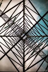 Symmetrical powerline tower from beneath